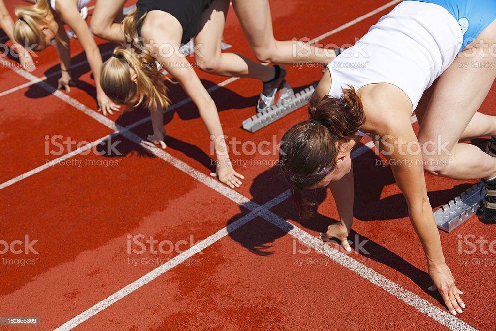 Female sprinters in starting blocks royalty-free stock photo