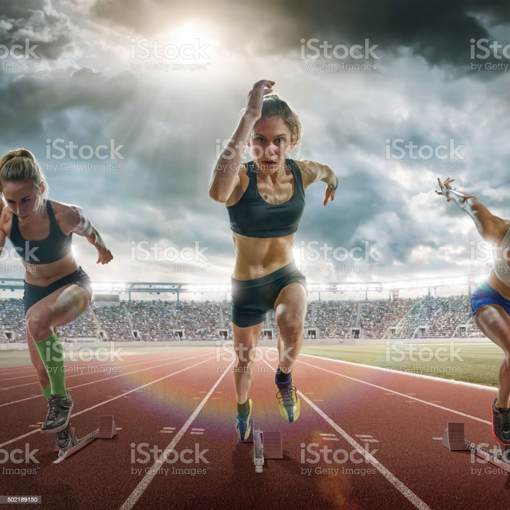 Female Sprinters Running Towards Camera During Race On Outdoor Track stock photo