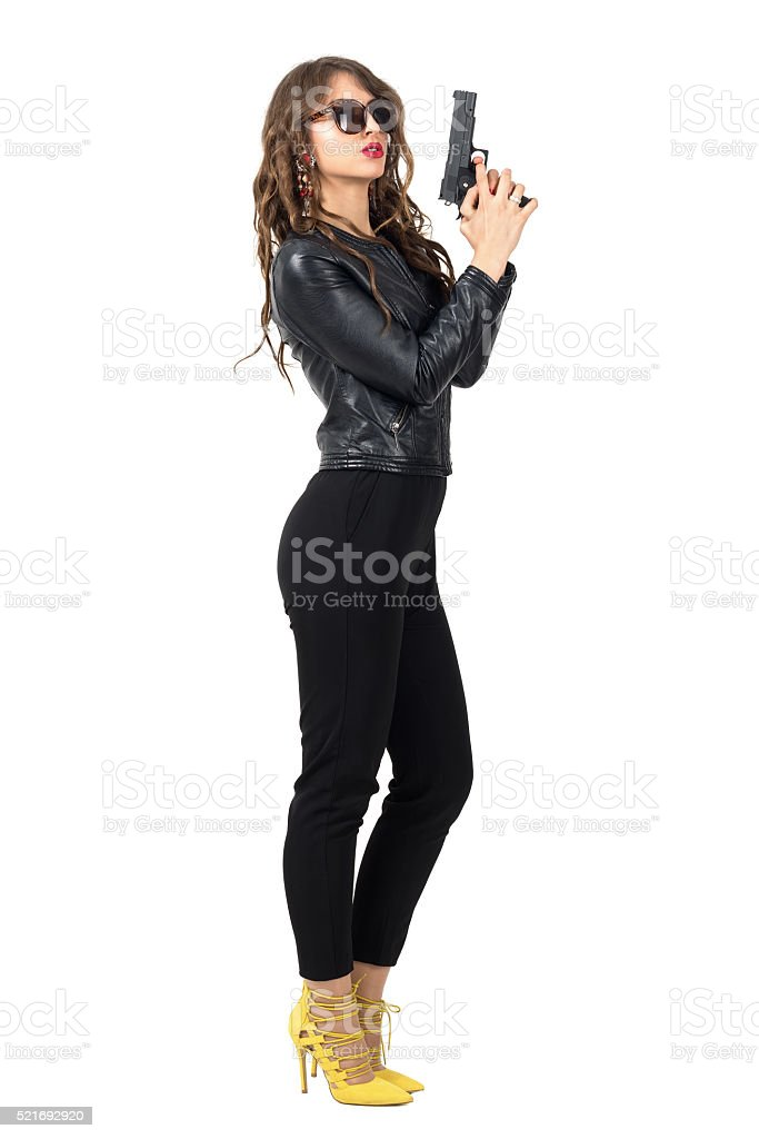 Female spy in leather jacket holding gun wearing sunglasses stock photo