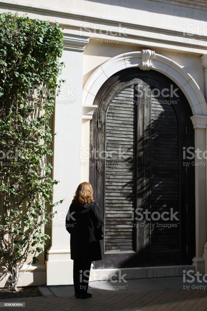 Female Standing by Huge Black Wooden Castle Door stock photo