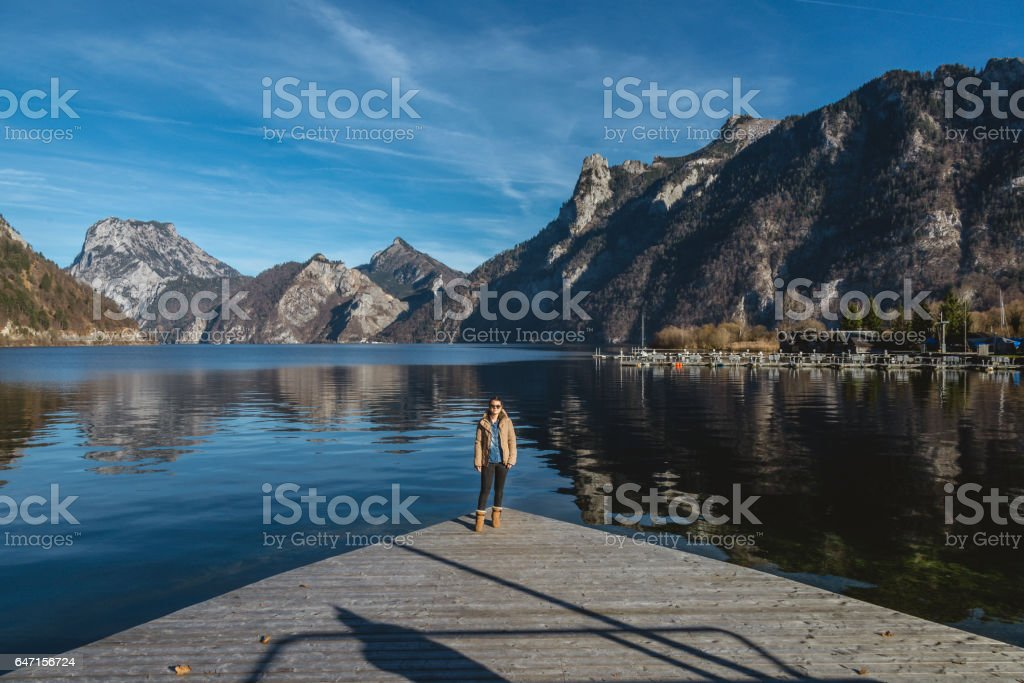 female standing on a dock in front of lake and mountains stock photo
