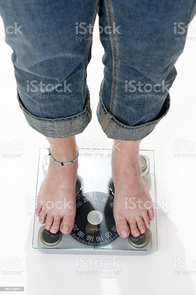 female standing on a scale royalty-free stock photo