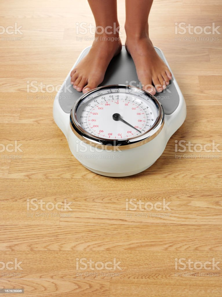Female Standing on Bathroom Scales royalty-free stock photo