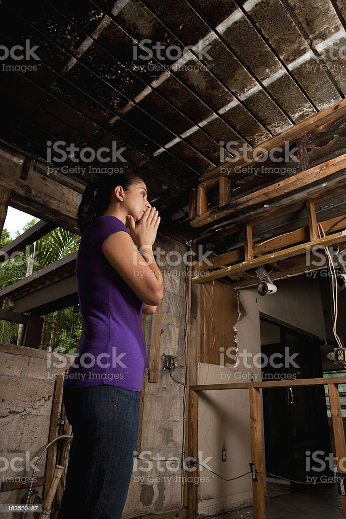 Female standing with hands on mouth inside house after fire stock photo