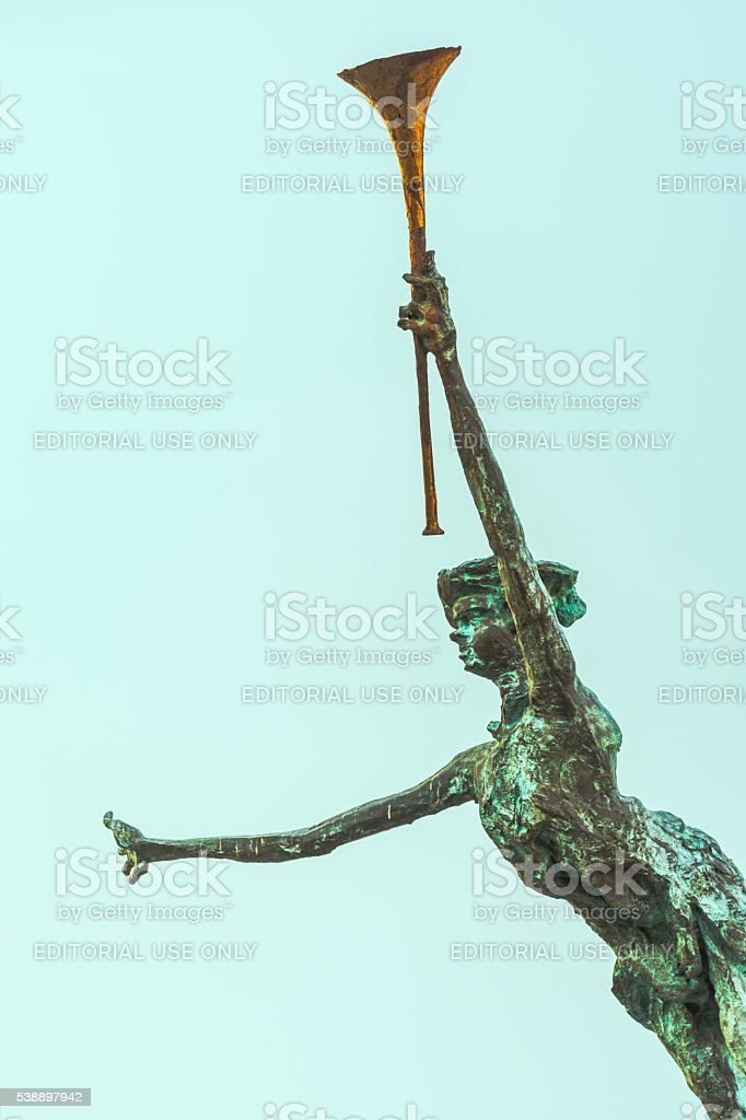 Female statue naked holding a gold trumpet in the air stock photo