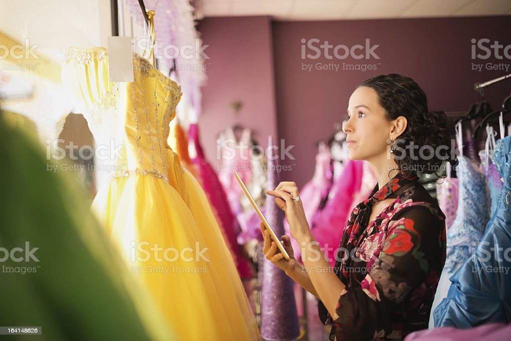 Female Store Owner Examining Gowns royalty-free stock photo
