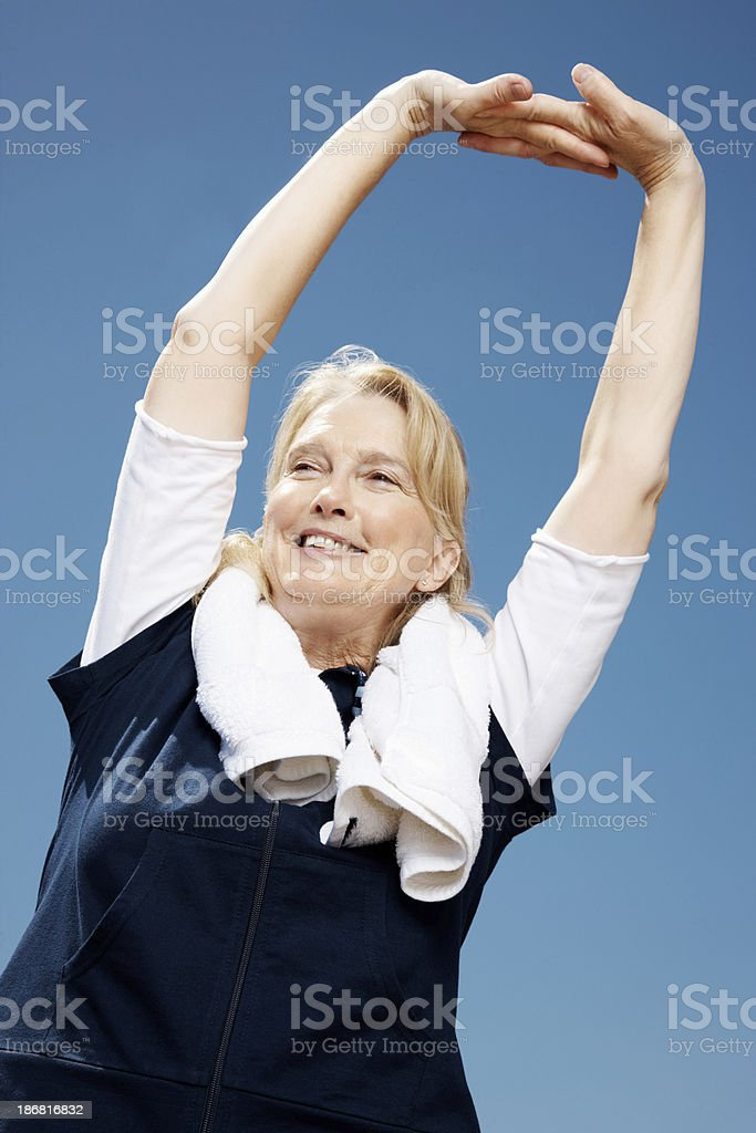 Female stretching her hands with a towel around neck royalty-free stock photo