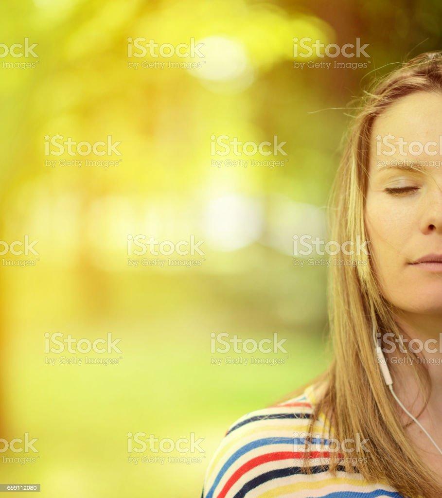Female student girl outside in park listening to music on headphones stock photo