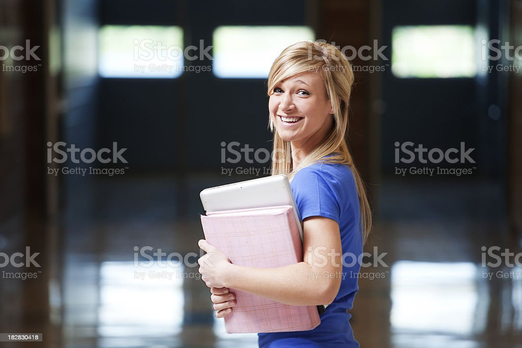 Female student in hallway, turning back at camera stock photo