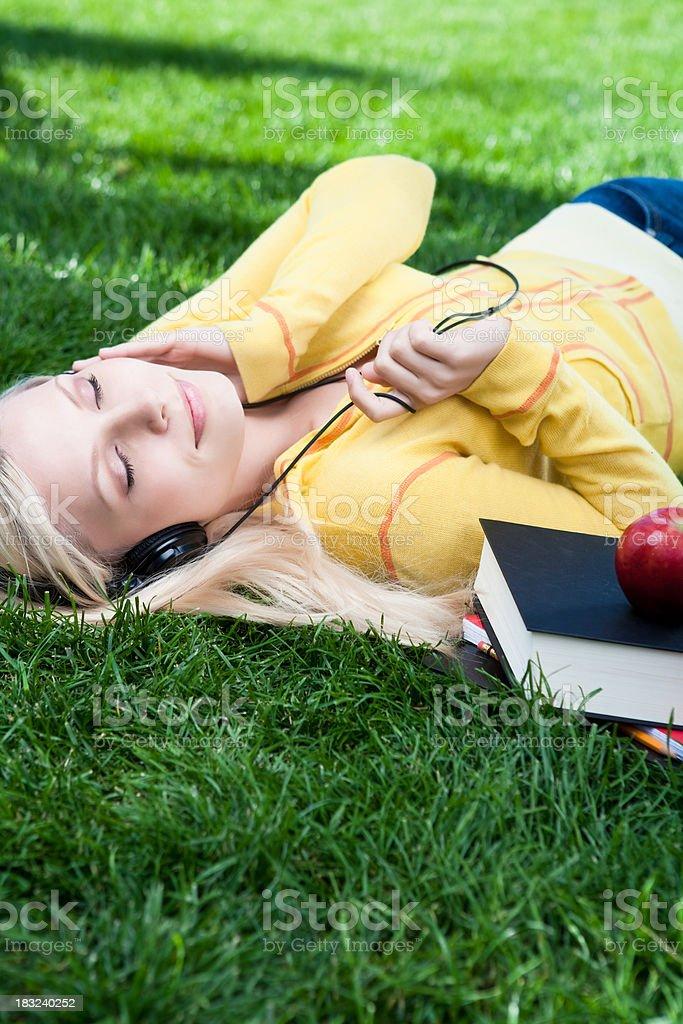 Female student listening to headphones royalty-free stock photo