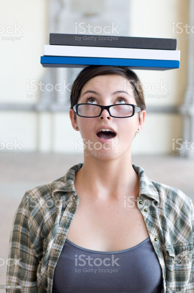 Female Student Looking Surprised Balancing Textbooks on Head royalty-free stock photo