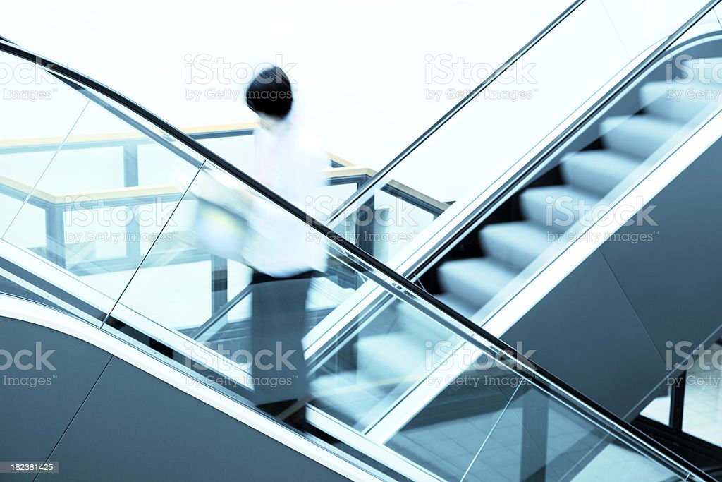 Female Student on Escalator, Blurred Motion royalty-free stock photo