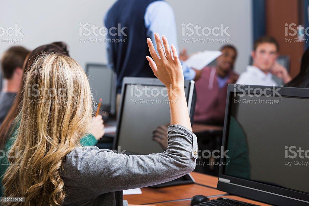 Female student raises hand in classroom stock photo