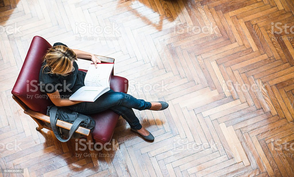 Female Student reading a book library stock photo