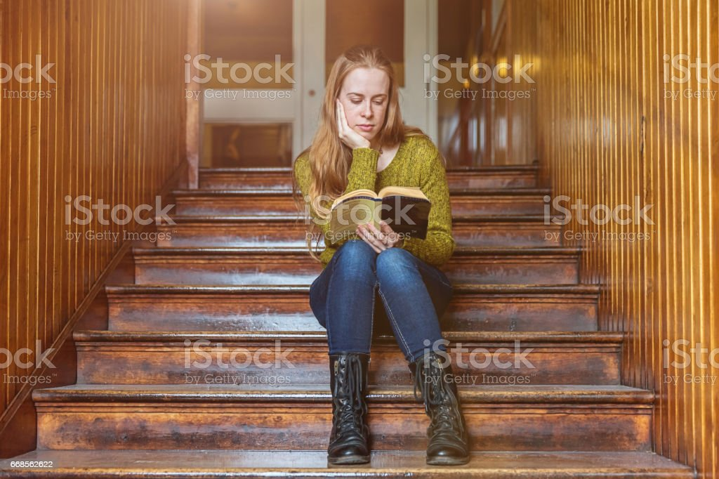 Female student reading book on wooden academy staircase stock photo