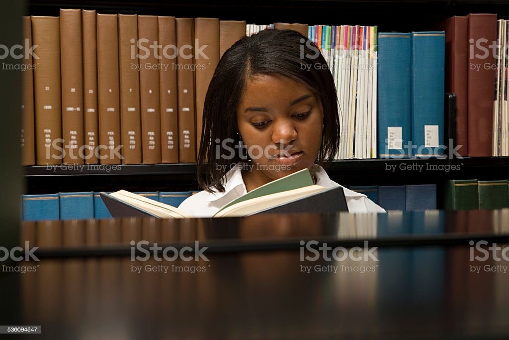 Female student reading in the library stock photo