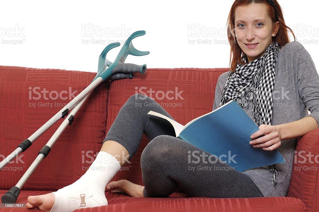 Female Student Reading on Sofa with Ankle Bandage
