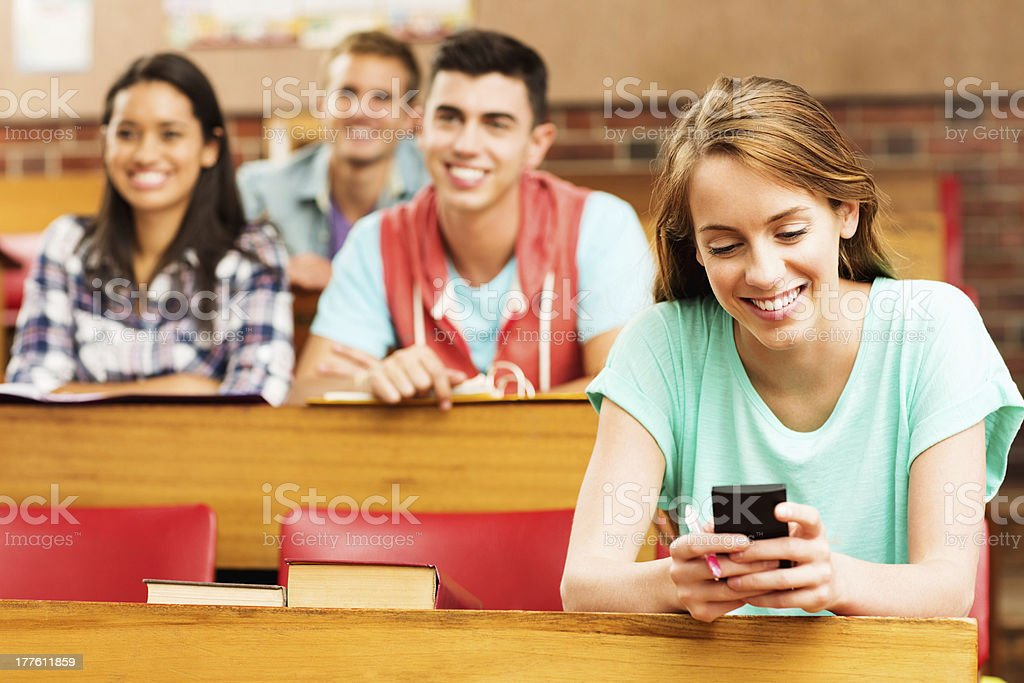 Female Student Reading Text Messaging While Sitting In Classroom royalty-free stock photo