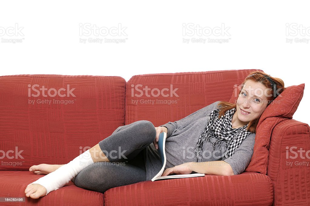 Female Student Resting on Sofa with Ankle Bandage royalty-free stock photo