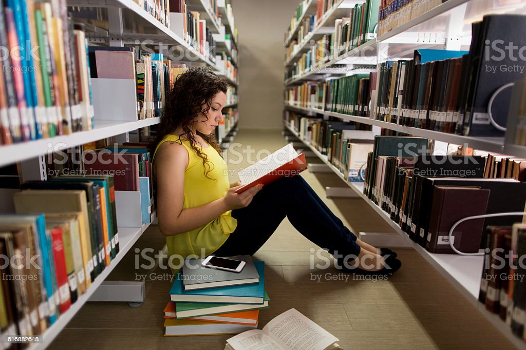 Female student sitting on the floor and reading a book stock photo
