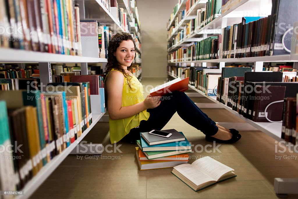 Female student sitting on the floor and smiling at camera stock photo