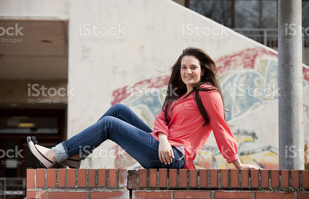 Female student sitting on wall stock photo