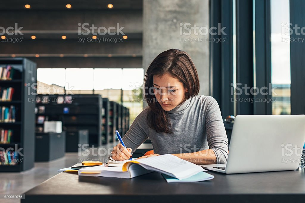 Female student studying at college library stock photo