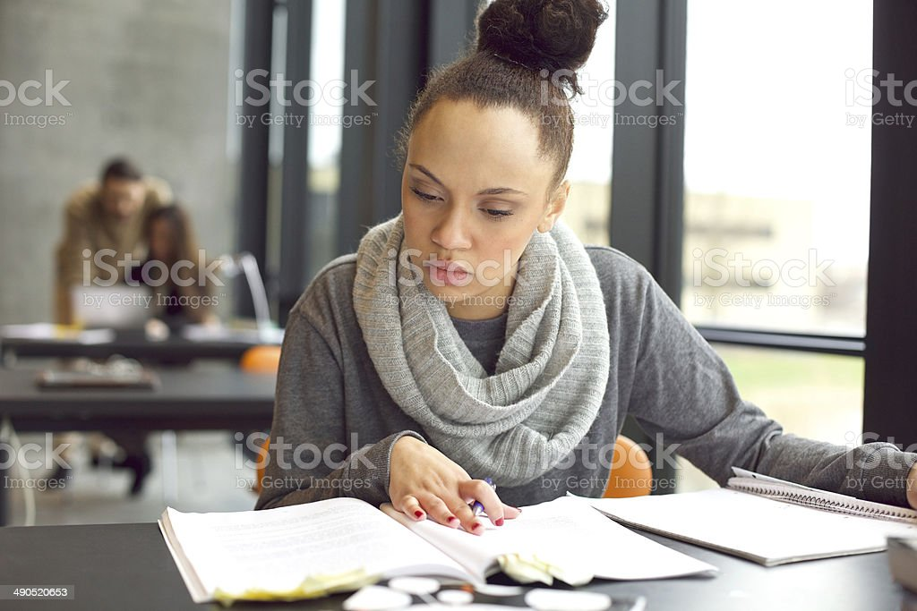 Female student studying in a library stock photo