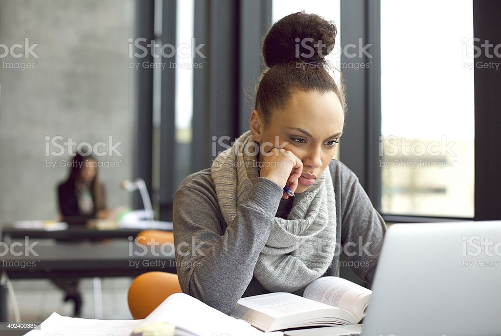 Female student studying in library with a laptop stock photo