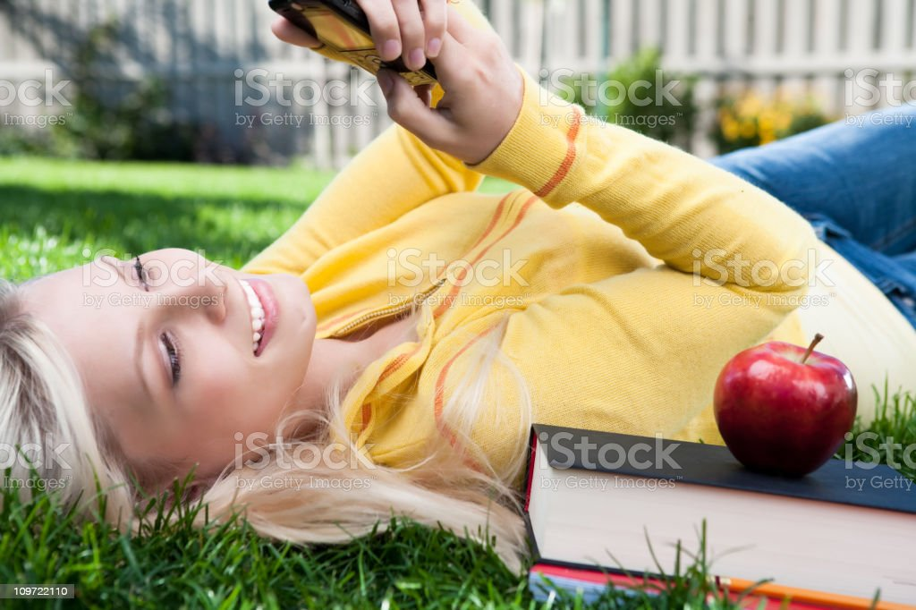 Female student texting laying on grass royalty-free stock photo