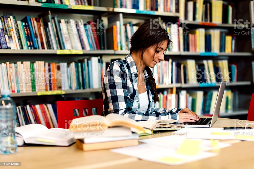 Female student using laptop for taking notes to study stock photo