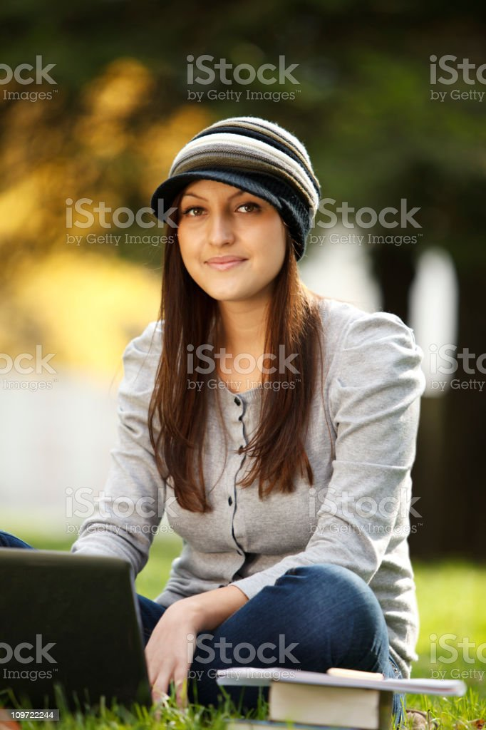 Female student using laptop in park royalty-free stock photo