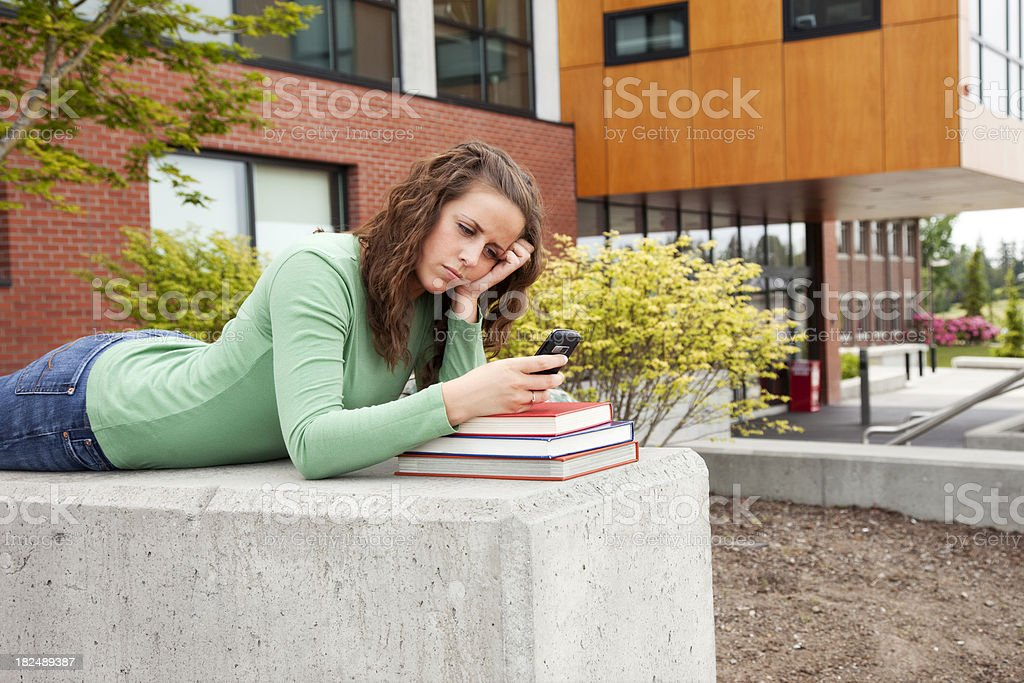 Female Student Waiting with Cell Phone royalty-free stock photo