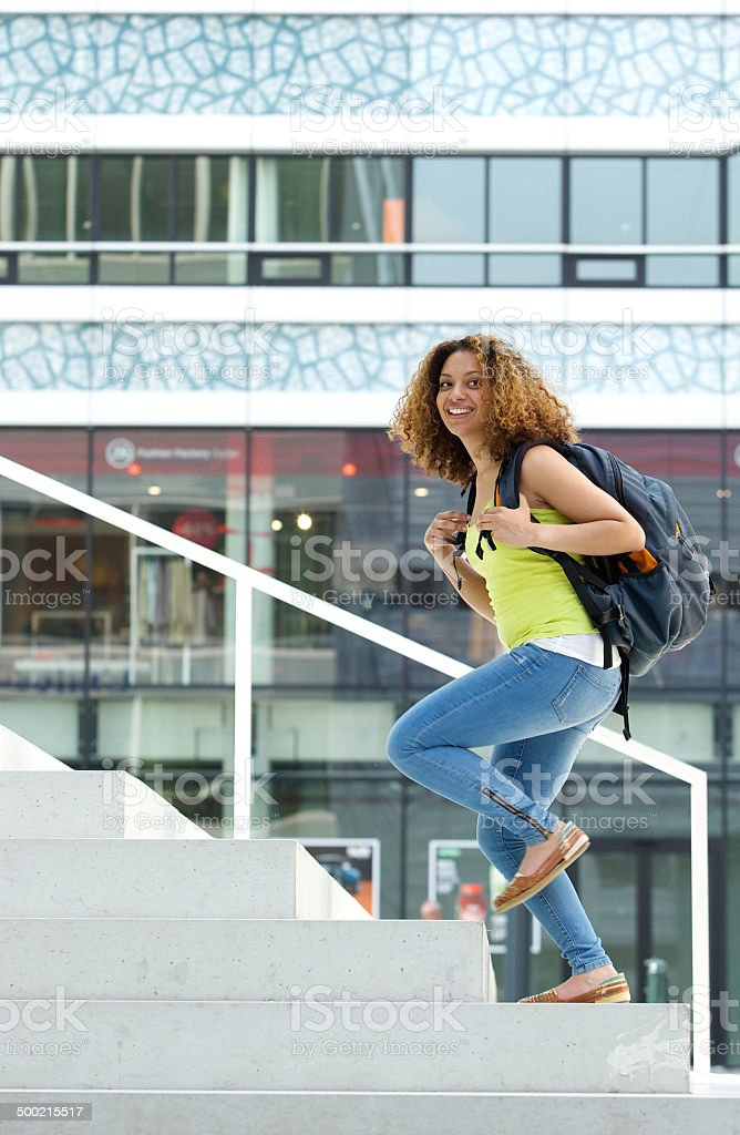 female student walking up stairs to college stock photo