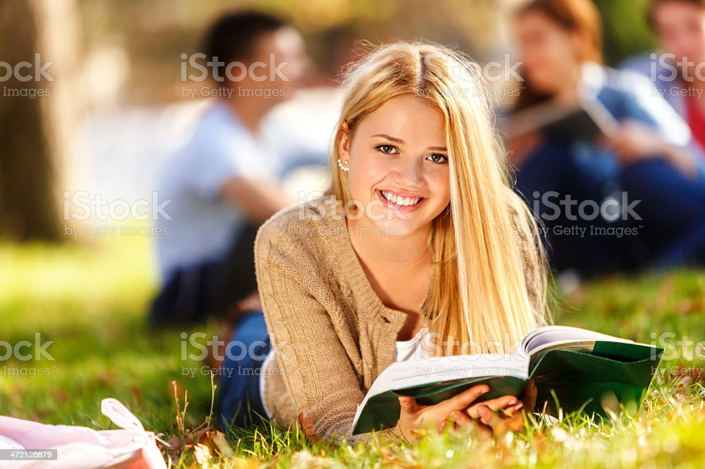 Female student with a book lying on a university campus royalty-free stock photo