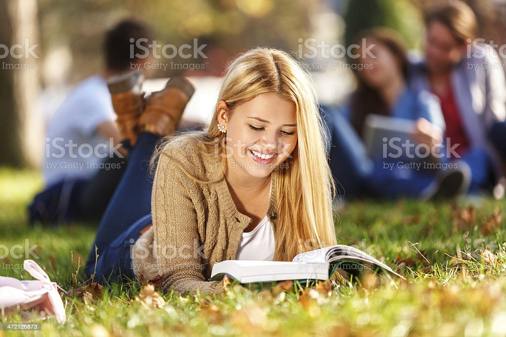 Female Student With Book Lying On University Campus royalty-free stock photo