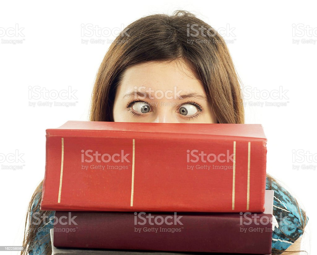 Female student with eyes crossed looking over stack of books royalty-free stock photo