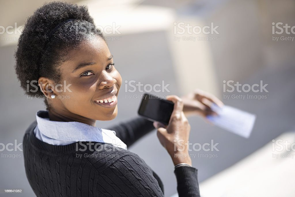 Female Student With Smart Phone Depositing Check stock photo