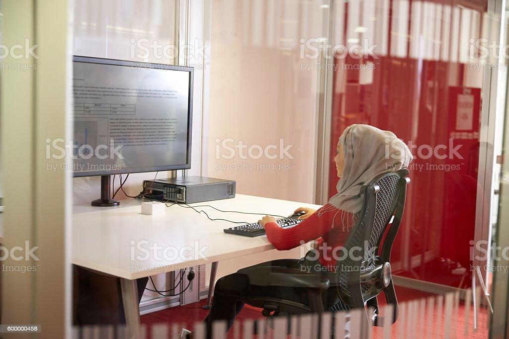 Female Student Working In Classroom With Large Screen stock photo