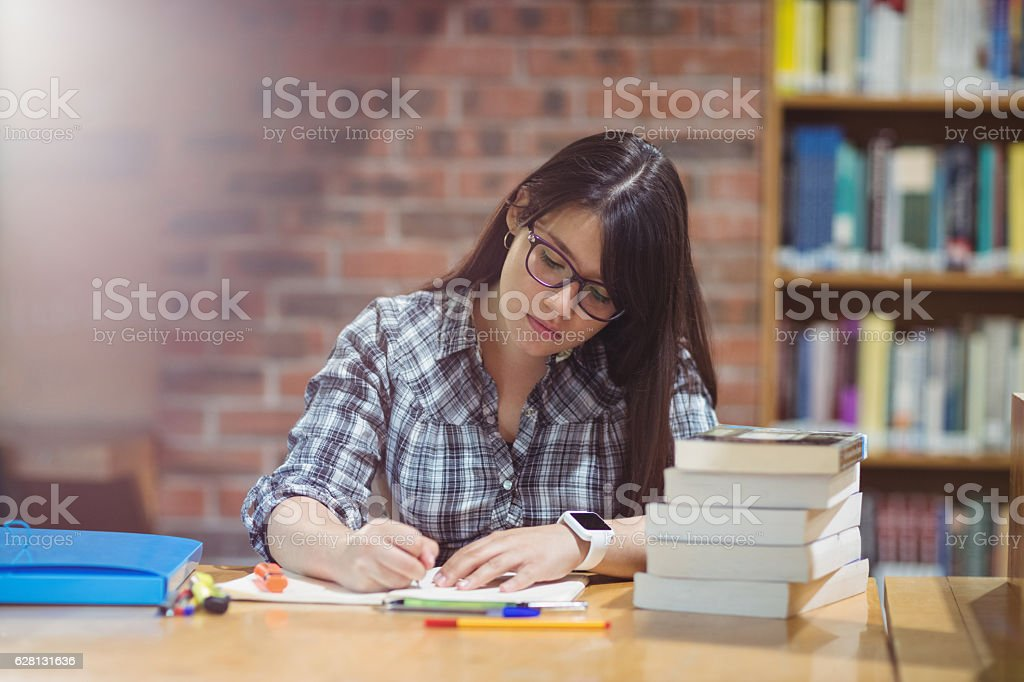 Female student writing notes in library stock photo