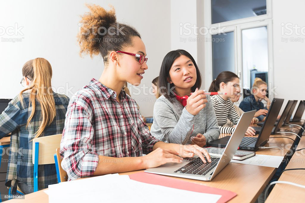 Female students learning computer programming stock photo