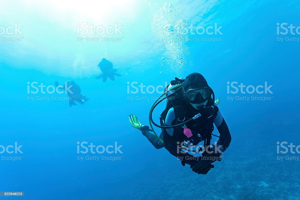 Female suba diver swimming under water stock photo