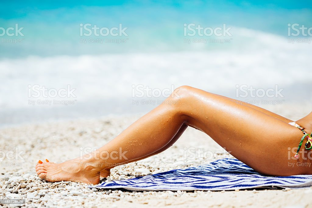 Female sunbathing legs on beach at sea shore in summer stock photo