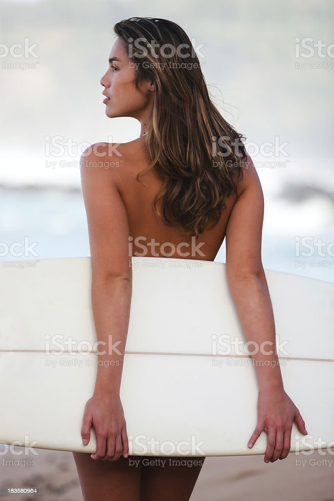 Female surfer posing on the beach with surfboard. royalty-free stock photo