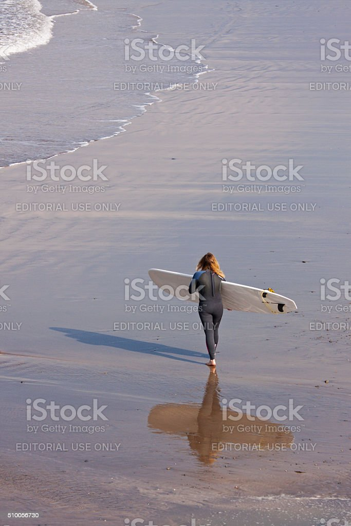 Female surfer walking along the sands UK stock photo