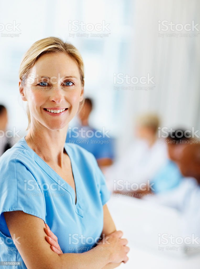 Female surgeon smiling with colleagues at the back royalty-free stock photo