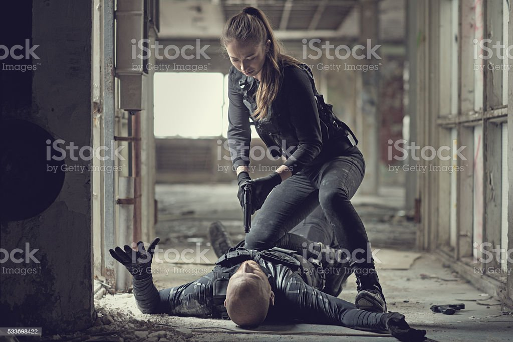 Female swat team member arresting male insurgent at gunpoint stock photo