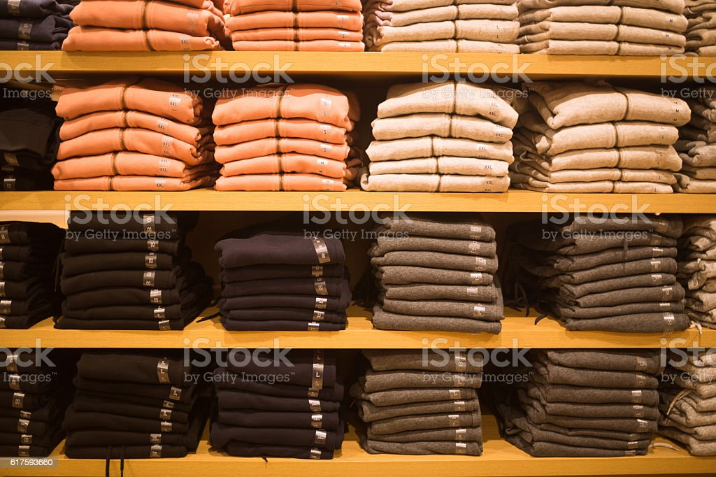 female  sweater stack in the shelf in the retail market stock photo