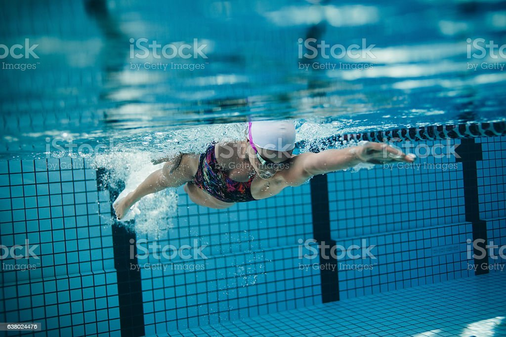 Female swimmer in action inside swimming pool stock photo