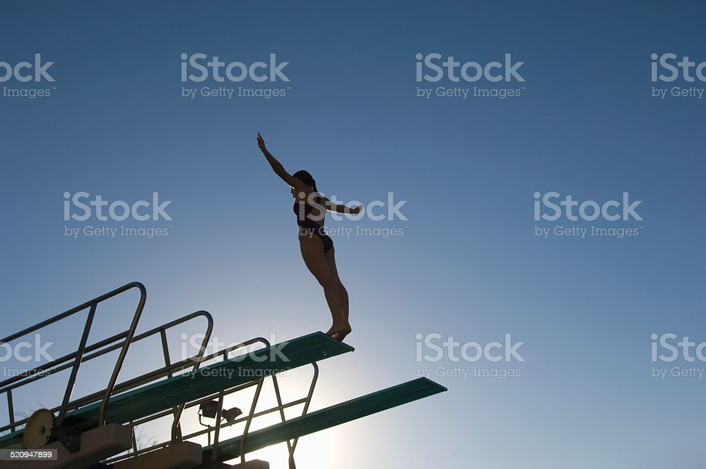 Female swimmer standing on diving board at sunset stock photo